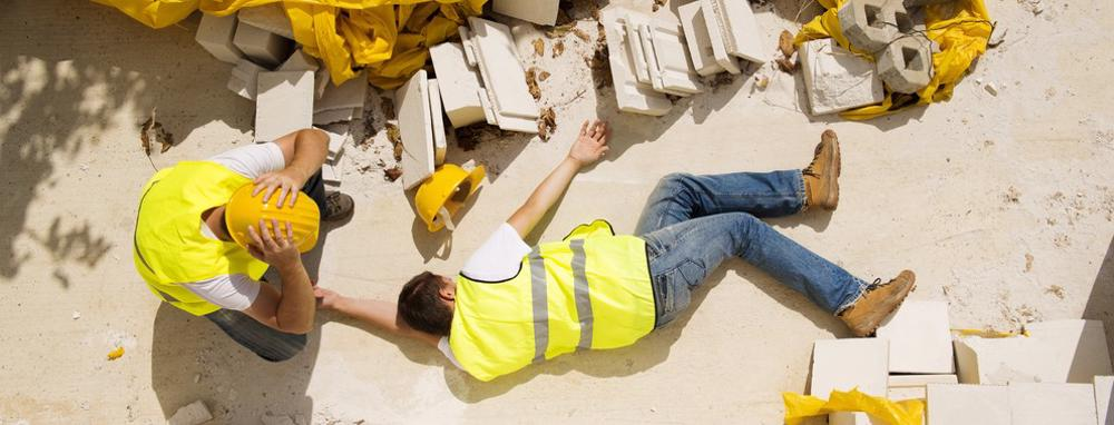 After a construction accident, a worker attends to an unconscious co-worker.