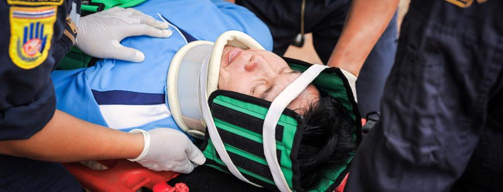 A man is loaded onto a stretcher with a neck stabilizer after a spinal cord injury