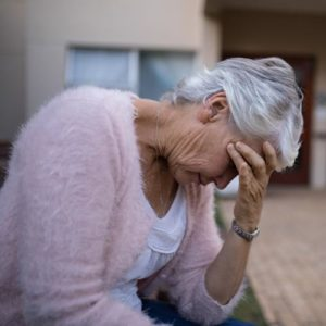 An elderly woman sits outside of a nursing home looking depressed