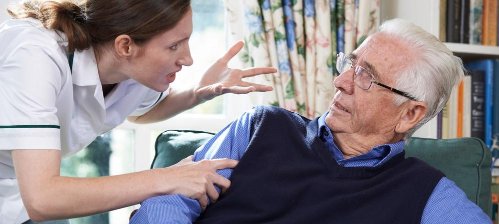 An elderly man is being yelled at by a nursing home employee