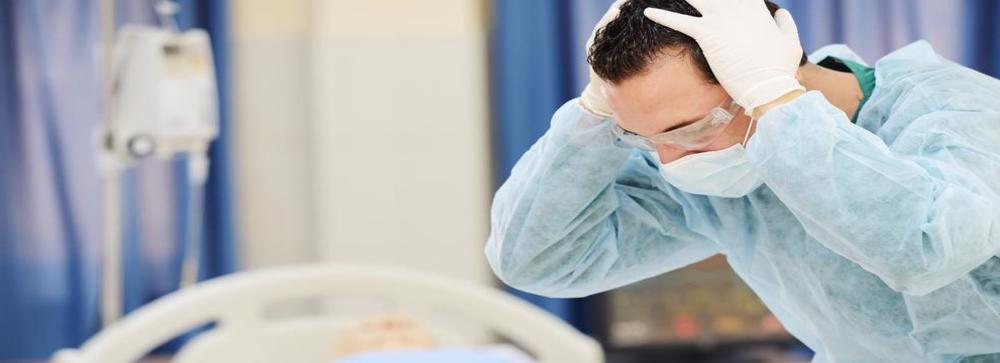 This image shows a doctor in shock after the wrongful death of a patient
