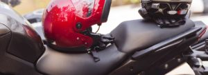 A picture of a motorcycle with 2 helmets on the seat so the riders are at no risk