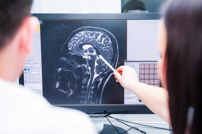 Doctors reviewing a brain scan indicating a catastrophic injury to an accident victim.