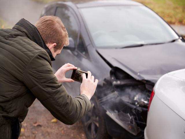 A man taking pictures of a Bessemer car accident scene to show his lawyer.