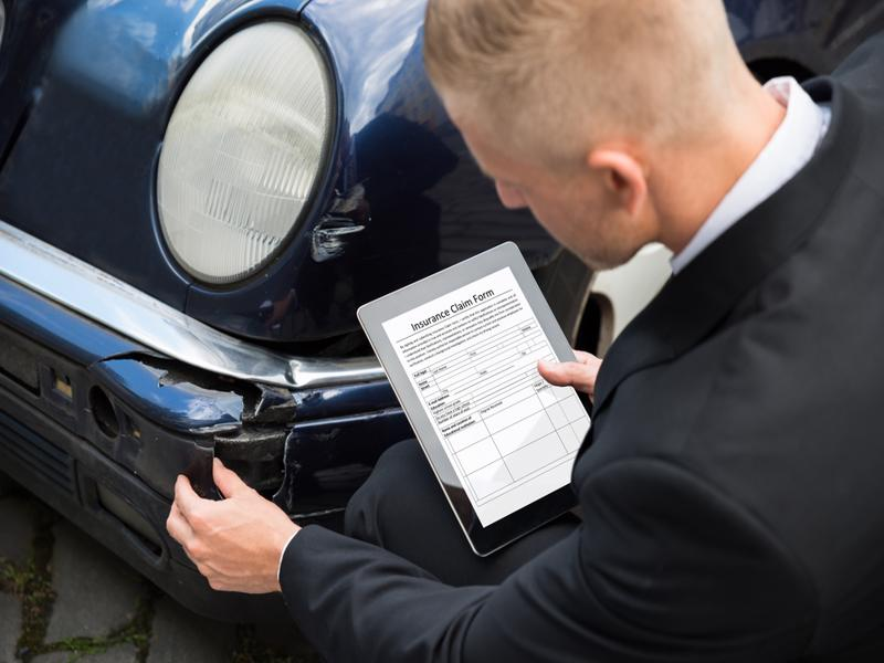 This image shows a Chelsea car accident lawyer documenting damages from an accident.