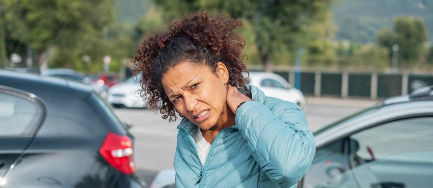 This image shows a woman holding her neck after being injured in a car accident in Chelsea, AL