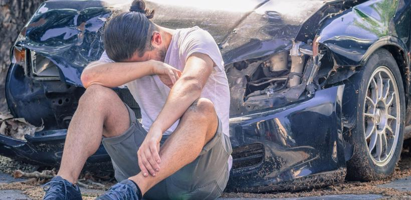 Man sitting in front of his car after an accident in Pell City, AL