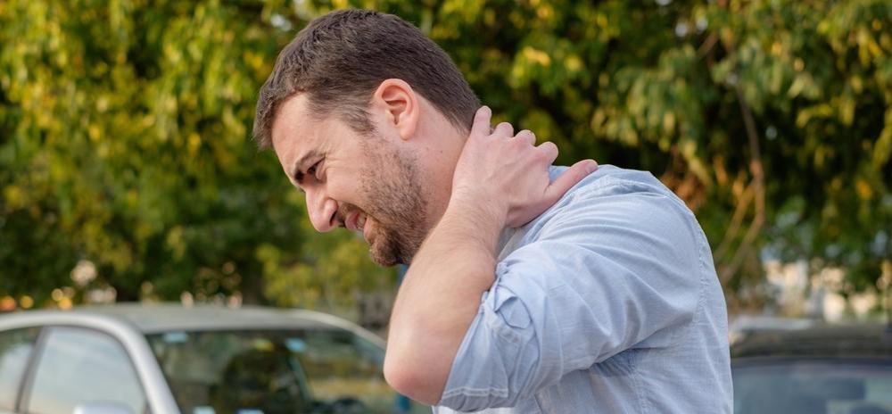 Man holding his neck after getting whiplash from a car accident in Pell City, AL