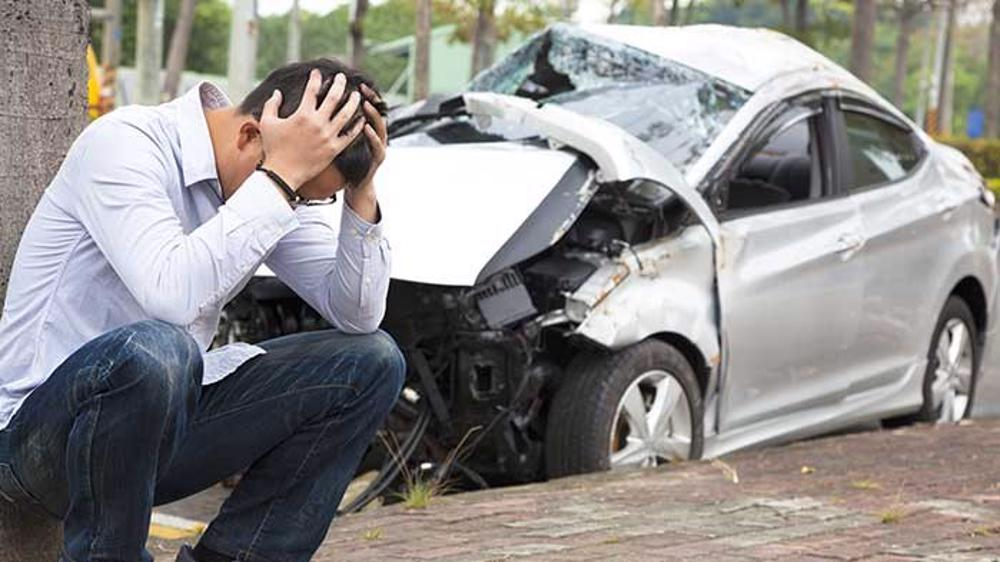 A man sitting outside of his car after a car accident in Siluria, AL