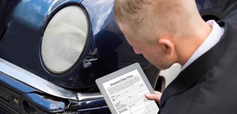 A Trussville car accident lawyer documenting damage for a car accident in Trussville, AL