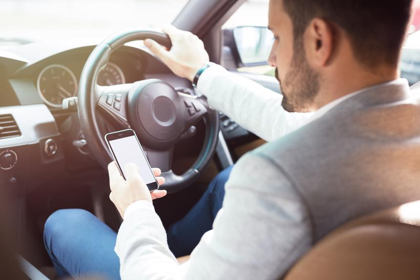 A man texting on his phone while driving.