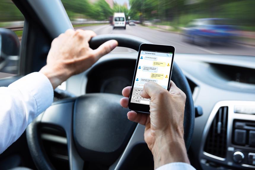 A man texting while driving his car.