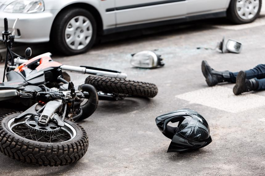 A helmet and motorcycle lying on the pavement next to a car it was involved in an accident with.