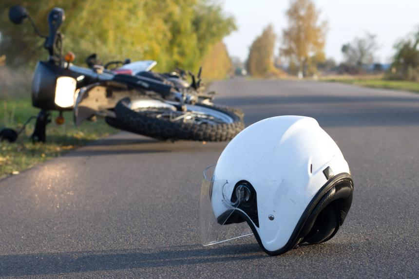 The aftermath of an accident, including a helmet and motorcycle lying in the road.