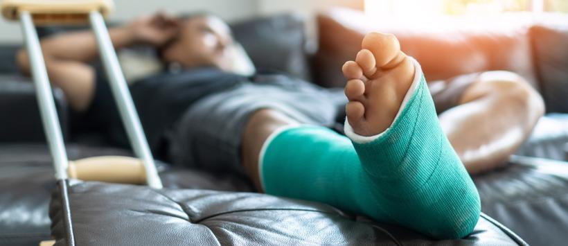 Injured man lying in bed with a cast on his leg in Culman, AL