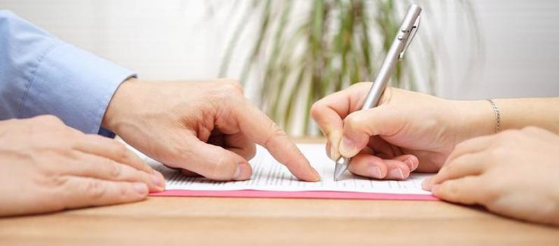 This image shows a client signing their documents with their Fairfield personal injury lawyer.