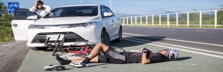 This image shows a bicyclist lying on the ground after being struck by another vehicle in Pell City, AL.