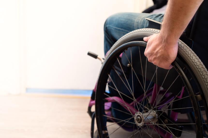 A person in a wheelchair after suffering a permanent disability from a spinal injury