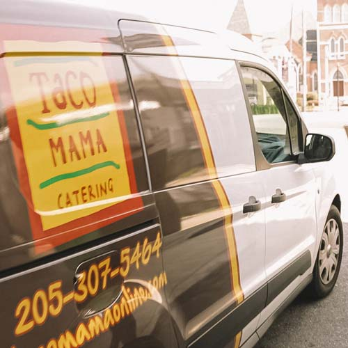 A Taco Mama van outside of a building.