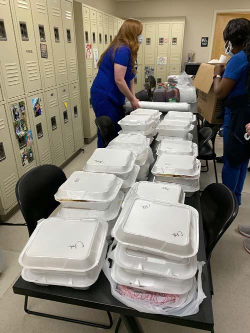 Two nurses preparing food.
