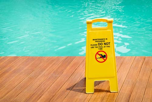 A safety sign placed by a swimming pool.
