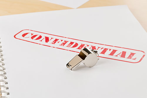 Chrome whistle on a paper with the word confidential