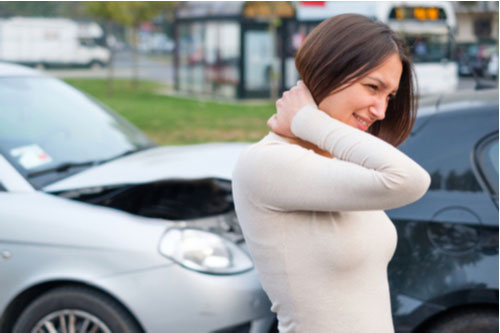 Young woman with whiplash rubbing neck after rear-end collision