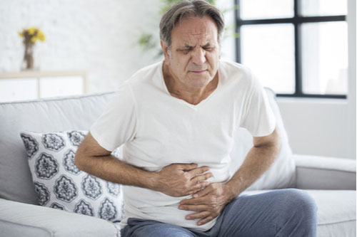 Senior man with stomach pain from defective hernia mesh