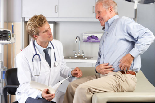 Doctor examining elderly man in pain from defective hip implant