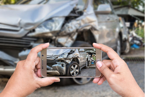 Close up of woman taking photo of car accident with smartphone
