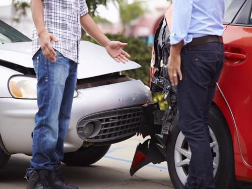 Two motorists exchanging information after a car accident.